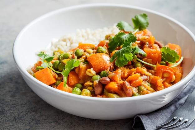 Veganistische curry met rijst in witte kom. curry met zoete aardappel, erwten en bonen in een bord met rijst.