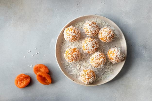 Veganistische energieballen met gedroogde abrikozen en kokos in keramische plaat veganistisch alternatief voedsel