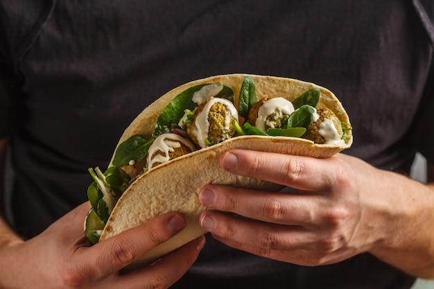 Veganistische falafel met groenten en tahinidressing in tortilla in handen van een man. veganistisch gezond eten, arabisch eten.