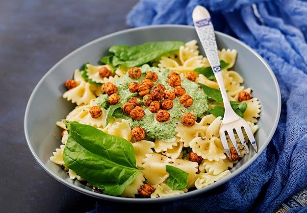 Veganistische farfalle pasta met spinaziesaus met gebakken kikkererwten