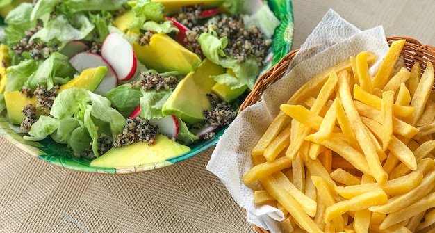 Veganistische groene salade met avocado, radijs, sla en quinoa. begeleid door een mooie portie frites.
