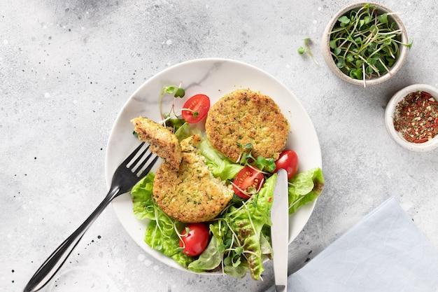 Veganistische hamburgers met quinoa, broccoli en salade in borden op lichte marmeren achtergrond