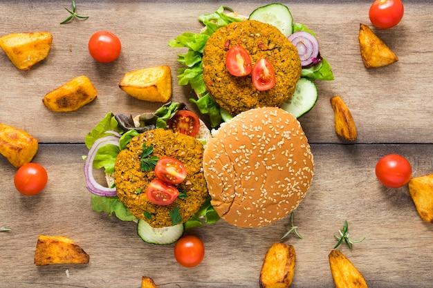 Veganistische hamburgers omgeven door aardappelen en tomaten