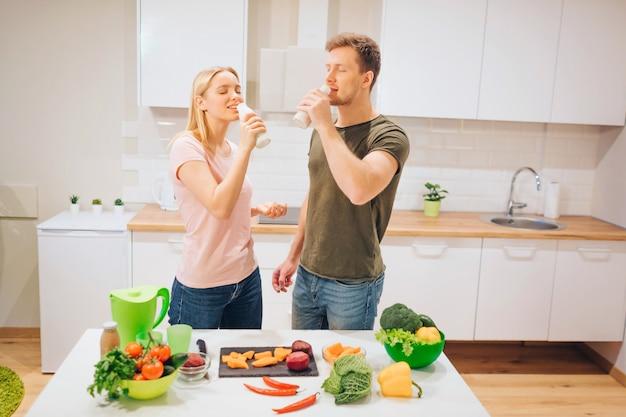 Veganistische jonge liefdevolle familie drinkt natuurlijke smoothie tijdens het koken van rauwe groenten in de keuken.