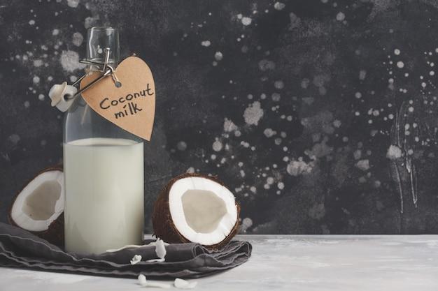 Veganistische kokosmelk niet-zuivelproducten in fles, kopie ruimte, donkere achtergrond. veganistisch gezond voedsel concept
