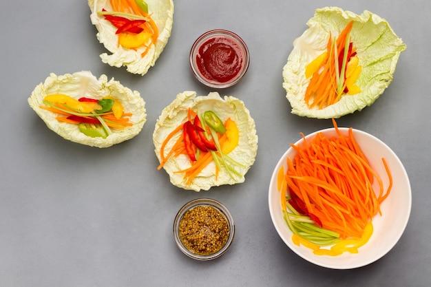 Veganistische koolbladhapjes met wortelen en mosterd en tomatensaus in kommen