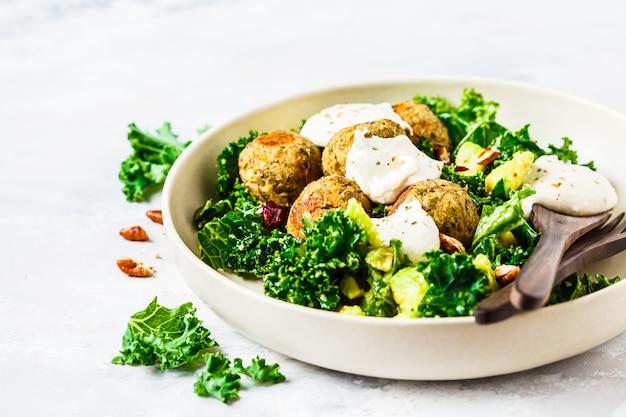 Veganistische linzengehaktballetjes met groene boerenkoolsalade, avocado en tahinidressing in een witte schotel.