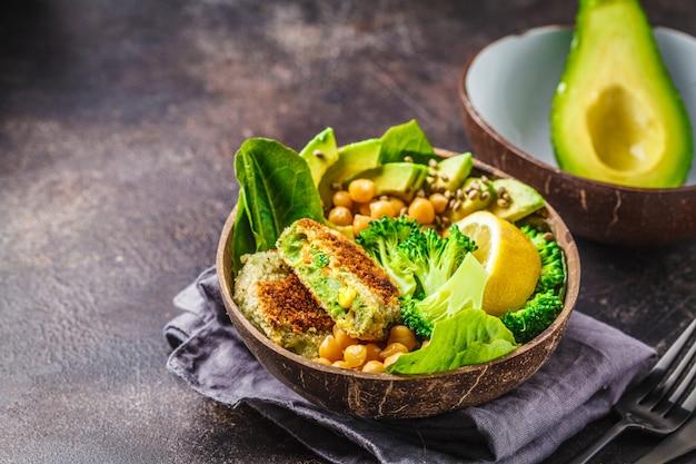 Veganistische lunch in een kom met kokosnoot: groene burgers met salade en kikkererwten.
