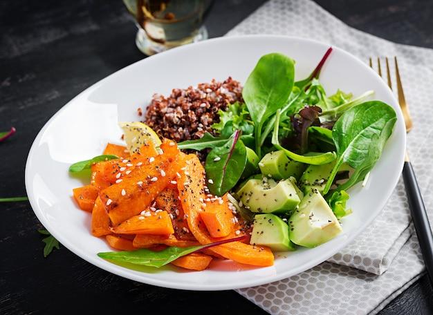 Veganistische maaltijden, lunch. buddha bowl met quinoa, gefrituurde schijfjes pompoen, avocado en groene kruiden