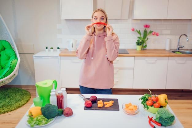 Veganistische mooie blonde vrouw heeft plezier met chili peper tijdens het koken van rauwe groenten in de keuken.