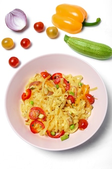 Veganistische noedels met erwten, paprika, ui en courgette