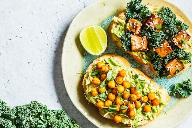 Veganistische open broodjes met guacamole, tofu, kikkererwten en spruitjes