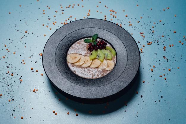 Veganistische pap. in gehydrateerde, plantaardige melk, banaan, honing, kiwi, granaatappel. op plaat geïsoleerd op blauwe achtergrond, close-up, bovenaanzicht