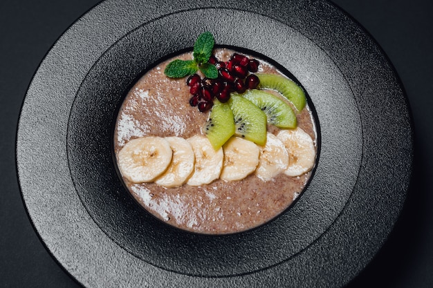 Veganistische pap. in gehydrateerde, plantaardige melk, banaan, honing, kiwi, granaatappel. op plaat geïsoleerd op zwarte achtergrond, close-up, bovenaanzicht