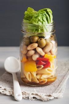 Veganistische pastasalade in glazen potten met groenten, bonen, olijven