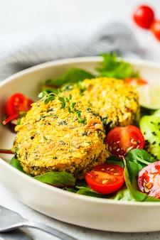 Veganistische pompoen en quinoa koteletten met salade in een witte plaat.