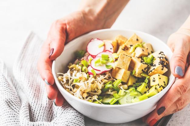 Veganistische porkom met ingelegde tofu, groenten en rijst in een witte kom.