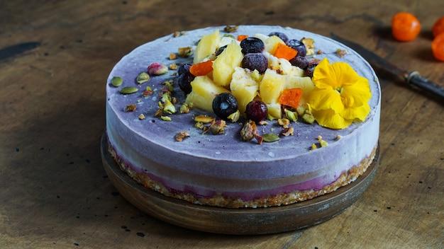 Veganistische rauwe cheesecake met bosbessen, kersen, matcha-thee, sinaasappel, cashew-room, kokosboter en kokosmelk, en basis gemaakt van amandelen, dadels en gedroogde abrikozen, havervlokken, gevriesdroogde bessen