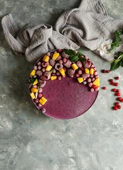 Veganistische rauwe cheesecake met bosbessen, kersen, matcha-thee, sinaasappel, cashew-room, kokosboter en kokosmelk en basis gemaakt van amandelen, dadels en gedroogde abrikozen