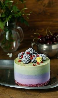 Veganistische rauwe cheesecake met bosbessen, kersen, matcha-thee, sinaasappel, cashew-room, kokosboter en kokosmelk