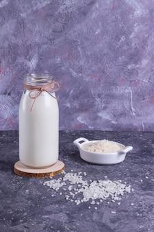 Veganistische rijstmelk in een glazen fles en rijst in een witte plaat op een houten standaard op een grijze achtergrond met een grijze servet