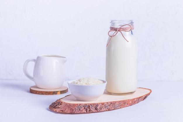 Veganistische rijstmelk in een glazen fles en rijst in een witte plaat op een houten standaard op een witte achtergrond