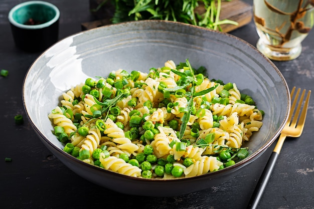Veganistische salade. fusilli-pasta met doperwten en uien. italiaans eten.
