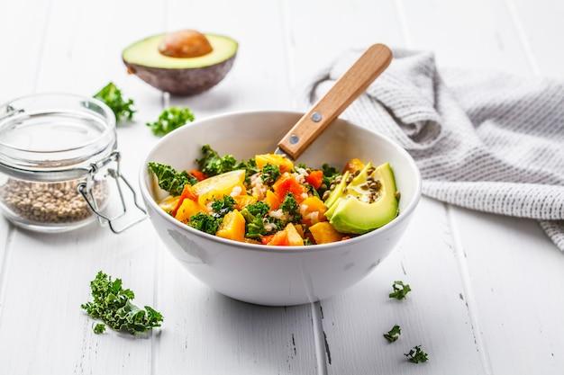 Veganistische salade met rijst, boerenkool, gebakken pompoen, wortelen en avocado
