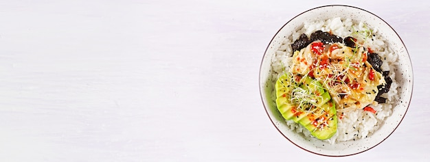 Veganistische salade met rijst, ingelegde kimchi-kool, avocado, nori en sesam op kom.