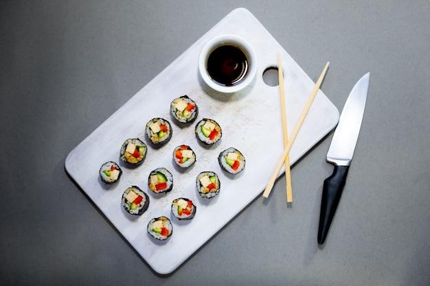Veganistische sushibroodjes met quinoagroenten en sojasaus op een wit bord