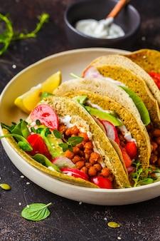 Veganistische taco's met gebakken kikkererwten, avocado, saus en groenten.