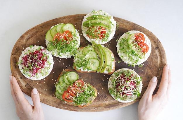 Veganistische toast gemaakt met microgreens op het houten bord in vrouwelijke handen