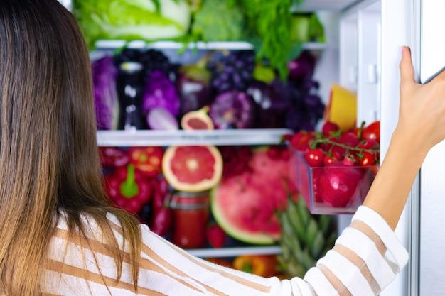 Veganistische vegetarische vrouw vrouw kiest voor gezonde antioxidant kleurrijke groenten, rauw sap en fruit om te eten na het openen van de koelkast in de buurt van met: grapefruit, tomaten, watermeloen, ananas, vijg.