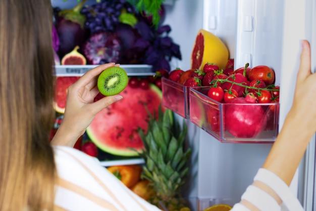 Veganistische vegetarische vrouw vrouwtje neemt groene gezonde antioxidant kiwi voor het eten na de markt in de buurt van koelkast met kleurrijke groenten, rauw sap en fruit: grapefruit, tomaten, watermeloen, ananas, vijg