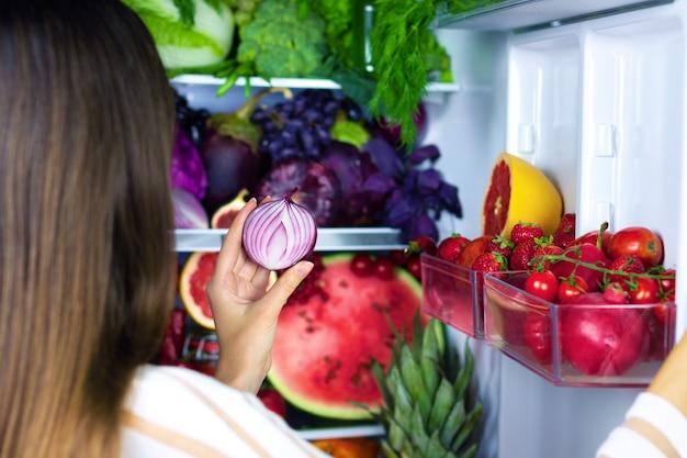 Veganistische vegetarische vrouw vrouwtje neemt violet gezonde antioxidant ui voor het eten na de markt in de buurt van koelkast met kleurrijke groenten, rauw sap en fruit: grapefruit, tomaten, watermeloen, ananas, vijgen
