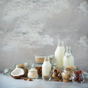 Veganistische vervangende zuivelmelk. glasflessen met niet-zuivelmelk en ingrediënten over gele achtergrond met exemplaarruimte.