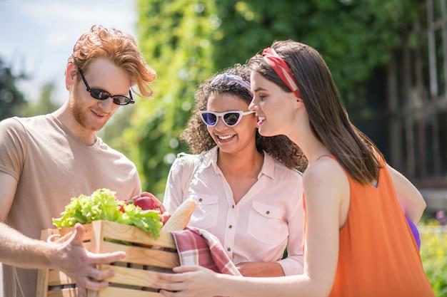 Vegetariërs. twee jonge mooie vriendelijke meisjes kijken naar groenten voor een picknick in handen van een lange man op mooie dag
