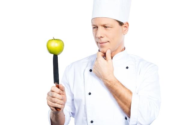 Vegetarisch eten koken. zelfverzekerde volwassen chef-kok in wit uniform met keukenmes met groene appel erop en ernaar kijkend terwijl hij tegen een witte achtergrond staat