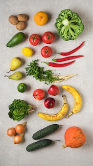 Vegetarisch eten. verse groenten, wortelgroenten en fruit op een grijze betonnen achtergrond. plat leggen, voedselfoto.