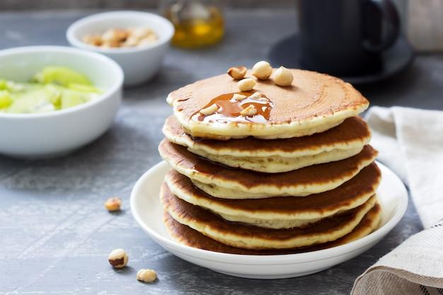 Vegetarisch ontbijt met pannenkoeken, koffie, honing, noten en fruit.