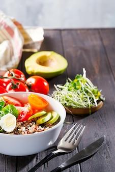 Vegetarisch ontbijt met quinoa, eieren, microgroen en groenten, groene thee met munt op een donkere houten tafel, plat leggen