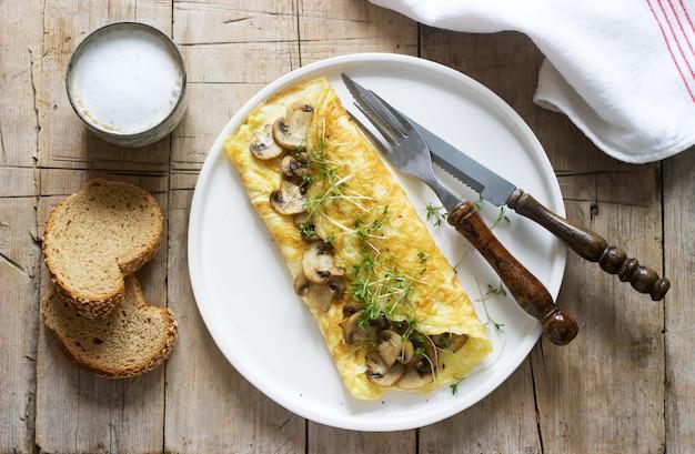 Vegetarisch ontbijt, omelet met champignons en tuinkers, geserveerd met roggebrood en koffie met melk. rustieke stijl.
