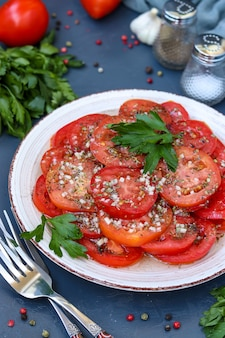 Vegetarisch voorgerecht van tomaten met knoflook, peterselie, gekleed met honing en olijfolie in een bord