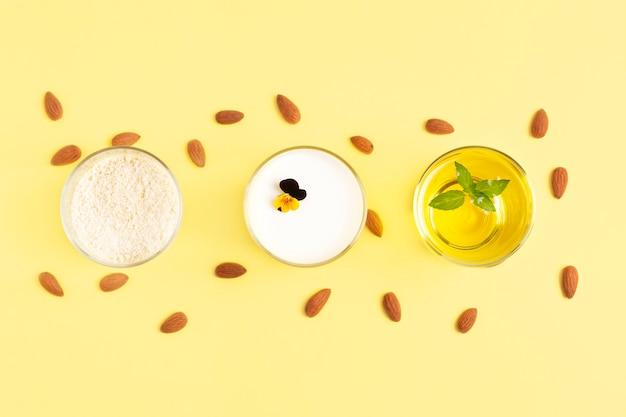 Vegetarische amandelproducten meel, boter, melk zijn in glazen op een gele kleur.