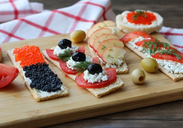 Vegetarische broodjes met gemengd voedsel op een houten bord.