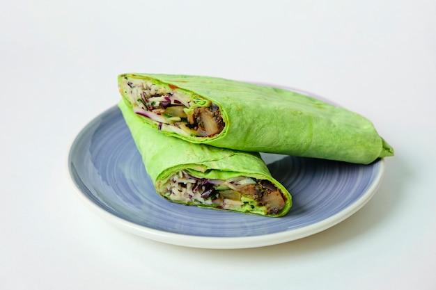 Vegetarische burrito donner van het sandwichbroodje in het groene tortilla verpakken op een plateba