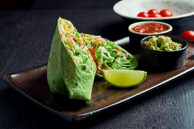 Vegetarische burrito met rijst, tomaten, maïs en paprika in groene pita op een bruin bord met tomatensalsa en guacamole. vegetarische shoarma roll