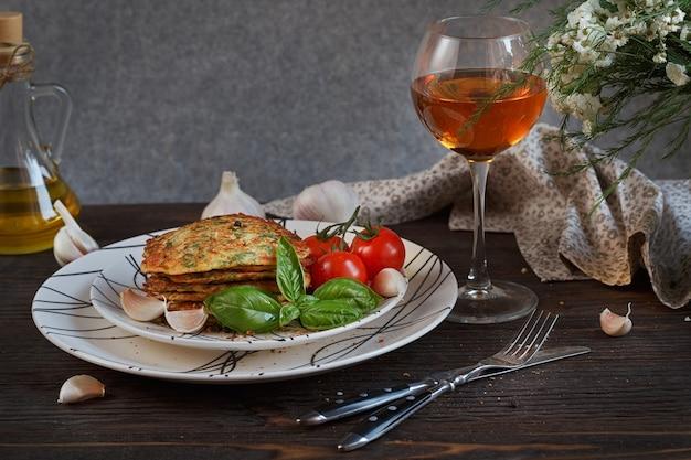Vegetarische courgette beignets geserveerd met verse kruiden, tomaten en knoflook
