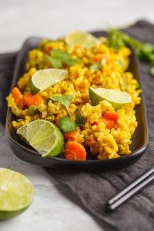 Vegetarische curryrijst met groenten en kokoscrème in een zwarte schaal. grijze achtergrond, kopieer ruimte. gezond veganistisch voedselconcept, detox, plantaardig dieet.