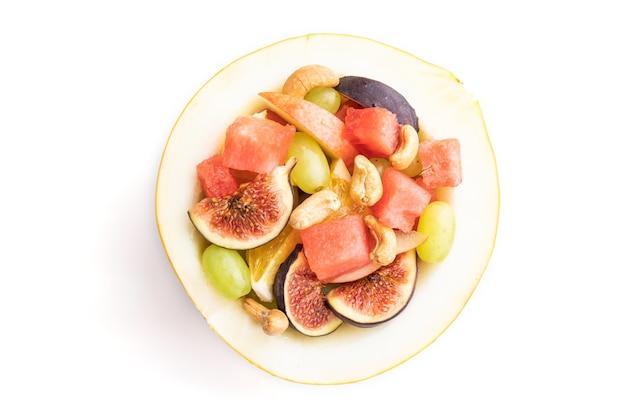 Vegetarische fruitsalade van watermeloen, druiven, vijgen, peer, sinaasappel, cashew geïsoleerd op een witte achtergrond. bovenaanzicht, plat leggen, close-up.